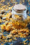 Bottles and dried calendula officinalis petals with macerated oil on wooden background. Royalty Free Stock Image