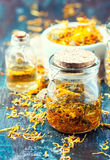 Bottles and dried calendula officinalis petals with macerated oil on wooden background. Stock Photos