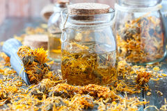 Bottles and dried calendula officinalis petals with macerated oil on wooden background. Stock Images