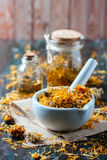 Bottles and dried calendula officinalis petals with macerated oil on wooden background. Royalty Free Stock Photos