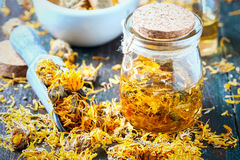 Bottles and dried calendula officinalis petals with macerated oil on wooden background. Royalty Free Stock Images