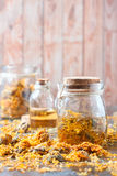 Bottles and dried calendula officinalis petals with macerated oil on wooden background. Royalty Free Stock Photo
