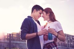 Pretty expressive young couple staying closely to each other stock photography
