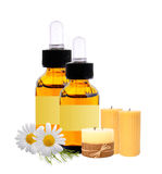 Bottles with essence oil, candles and chamomiles isolated on whi Stock Photos