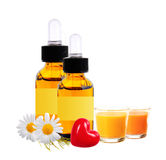 Bottles with essence oil, chamomiles and candles isolated Royalty Free Stock Images
