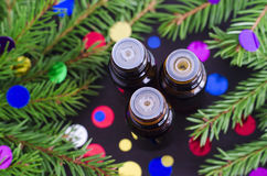 Bottles of essential oil and fir branches. Christmas aromatherapy and spa concept. Royalty Free Stock Photos