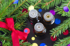 Bottles of essential oil and fir branches. Christmas aromatherapy and spa concept. Stock Images