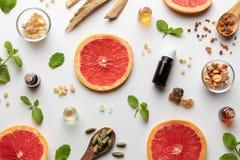 Bottles of essential oil with fresh grapefruit, peppermint, myrrh, white sandalwood, frankincense, cardamon royalty free stock photo