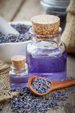 Bottles of essential oil, wooden spoon with dry lavender flowers Royalty Free Stock Images