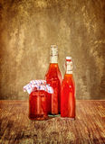 Bottles filled with yellow syrup and jam on kitchen table Stock Photos