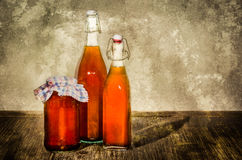 Bottles filled with yellow syrup and jam on kitchen table Royalty Free Stock Photography