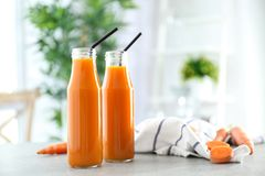Bottles of fresh carrot juice. On blurred background Royalty Free Stock Photography