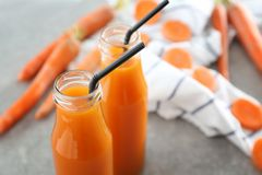 Bottles of fresh carrot juice. On grey background stock photos