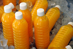 Bottles of Fresh Orange Juice on Ice. Closeup image of plastic bottles of fresh orange juice on ice cubes in the container Royalty Free Stock Photos