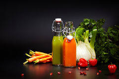Bottles with fresh vegetable juices. Isolated on black. Detox diet royalty free stock photos