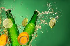Bottles of fruit beer with splash, on gree Royalty Free Stock Photo