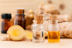 Bottles of ginger oil and ginger on wooden background. Royalty Free Stock Photo