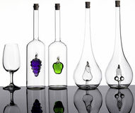 Bottles and glass. Artistically bottles with glass fruits inside Royalty Free Stock Photography