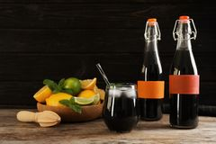 Bottles and glass with natural charcoal lemonade on table royalty free stock images