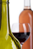 Bottles and glass poured with red wine  on white Stock Photos