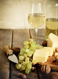 Bottles and glass of white wine, cheese, nuts and grapes Stock Images