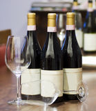 Bottles and glasses. Three bottles of wine and two glasses over a wooden table Royalty Free Stock Photos