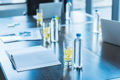 Bottles and glasses with antioxidant drink for business meeting on table in workspace stock photos