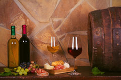 Bottles and glasses of red and white in wine cellar, old wine barrel. Bottles and glasses of red and white wine with cheese, prosciutto and grape in wine cellar stock images
