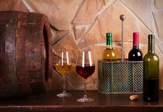 Bottles and glasses of red and white in wine cellar, old wine barrel. Food and drinks concept royalty free stock photo