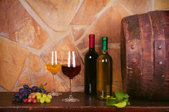 Bottles and glasses of red and white in wine cellar, old wine barrel. Bottles and glasses of red and white wine with grape in wine cellar, old wine barrel. Food royalty free stock images