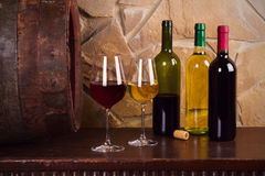Bottles and glasses of red and white in wine cellar, old wine barrel. Food and drinks concept stock images