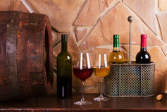 Bottles and glasses of red and white in wine cellar, old wine barrel. Food and drinks concept stock photography