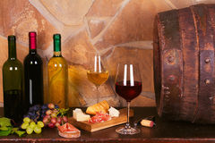Bottles and glasses of red and white in wine cellar, old wine barrel. Bottles and glasses of red and white wine with cheese, prosciutto and grape in wine cellar stock photography