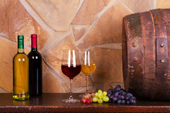Glasses of red and white wine in wine cellar, old wine barrel. Bottles and glasses of red and white wine with grape in wine cellar, old wine barrel. Food and stock image