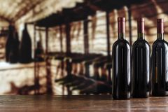 Bottles and glasses of wine in the cellar. Red wine in a glass on the background of a cellar, vintage picture for a wine card stock photography