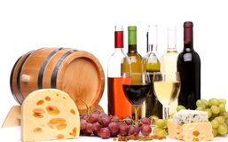 Bottles and glasses of wine and ripe grapes. Barrel, cheeses, bottles and glasses of wine and ripe grapes on wooden on a white background Stock Image