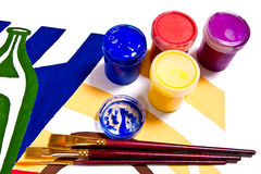 Bottles with gouache paints and different kinds of brushes. Stock Image