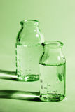 Bottles on green. A photo of two glass measure bottles on green Royalty Free Stock Photography