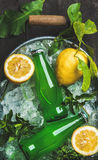 Bottles of green lemonade on chipped ice in metal tray Stock Image