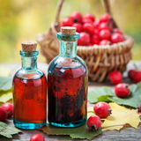Bottles of hawthorn berries tincture and red thorn apples. In basket on wooden table with autumn maple leaves. Herbal medicine. Selective focus Stock Images