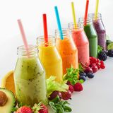 Bottles of healthy fresh veg and fruit smoothies. Bottles of assorted healthy fresh vegetable and fruit smoothies in a receding diagonal row with straws and copy Royalty Free Stock Photography
