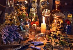 Bottles with herbs, lavender flowers, paper scrolls and magic objects on witch table. Occult, esoteric, divination and wicca concept. Mystic and vintage stock photo