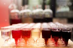 Bottles with homemade tinctures and glasses on the table stock photo