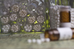 Bottles with homeopathy globules. Focus in homeopathy pills and variety of bottles Royalty Free Stock Photography