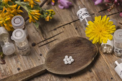 Bottles with homeopathy globules and spoon, decorated with flowe Royalty Free Stock Photography