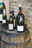 Bottles of Italian wine over wooden barrel. Stock Photos
