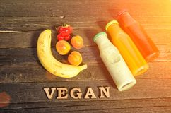 Bottles with juice, fruit and inscription Vegan on a wooden background, food concept Stock Images