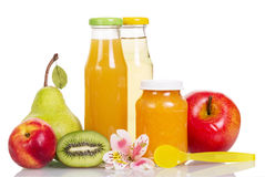 Bottles juice and jar pureed fruit, spoon, orchid flower. Royalty Free Stock Images