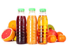 Bottles of juice  with ripe fruits Royalty Free Stock Photo
