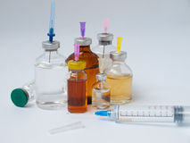 Bottles of medicine and a large syringe Stock Images